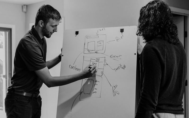 decorative image of two people working on and looking at a diagram on a white board